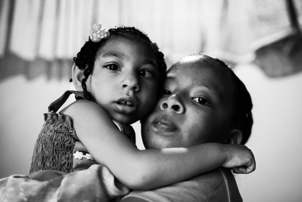 """Brianna, 8, holds her sister Samara at their house, in Santa Elena neighborhood, south of Cali. """"I love to play with my sister when I arrive from school"""", Brianna says. November 20, 2019."""