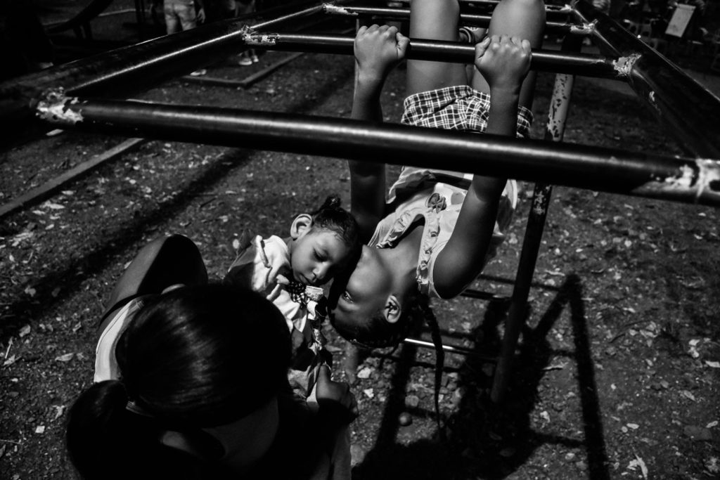 Brianna, who is headlong in a handrail, kisses her sister Samara in Santa Elena neighborhood's park, close to their house. April 28, 2019.